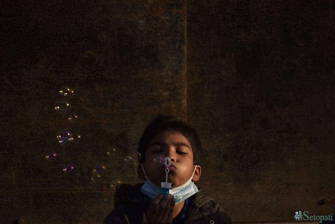 भक्तपुरको पोटरी स्क्वायरमा 'सोप बबल' उडाँदै एक बालक। तस्बिरः नारायण महर्जन