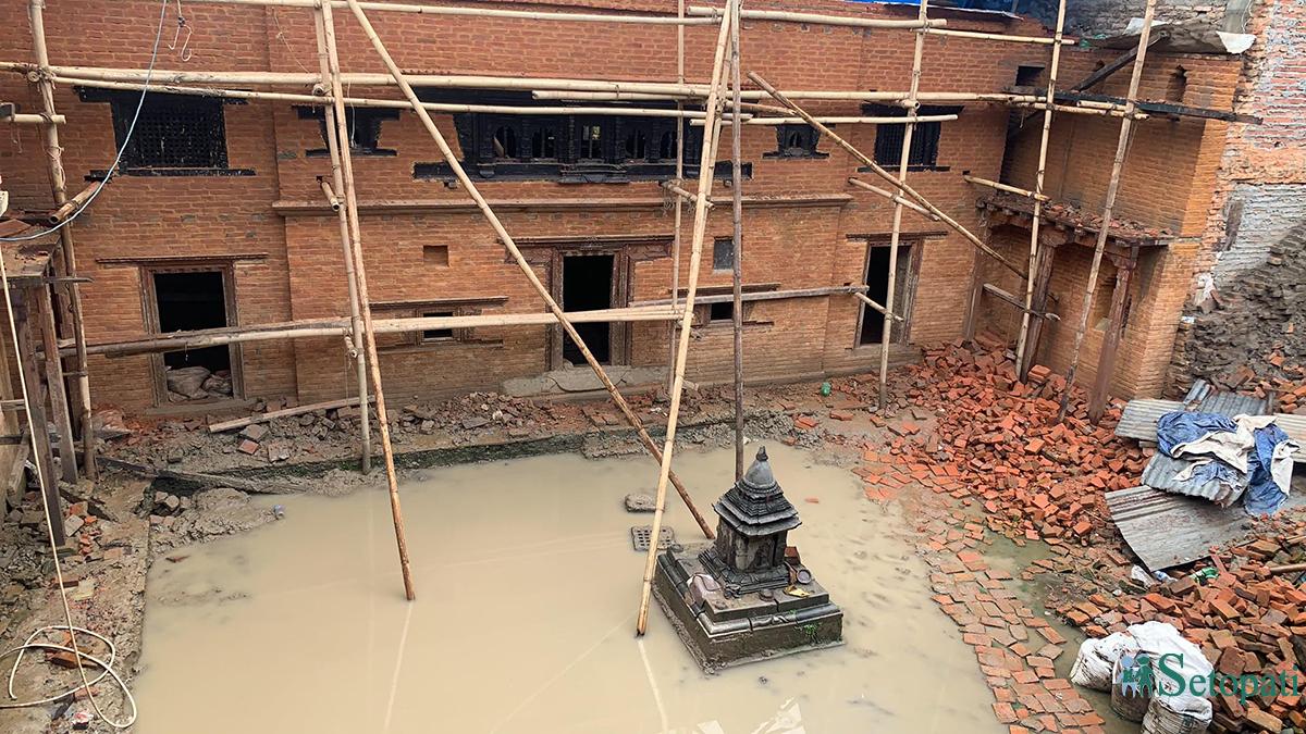 भक्तपुरको मध्यपुर थिमि ६ स्थित पुननिर्माण हुँदै गरेको दथुबहा: (जेतवर्ण महाविहार) अगाडि जमेको पानी। तस्बिरः सेतोपाटी