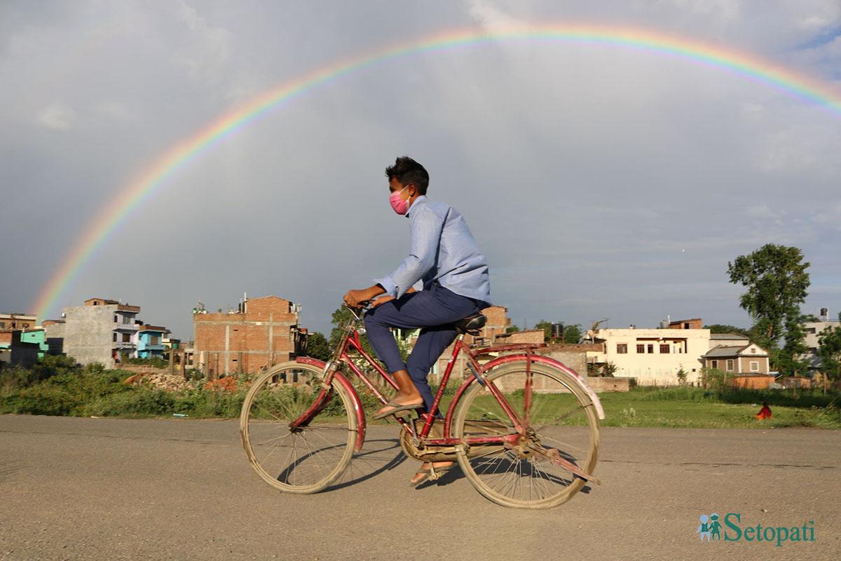 शनिबार बेलुका दाङको आकाशमा देखिएको इन्द्रेणी र साईकल चलाएर गन्तब्यमा जाँदै गरेका एक विद्यार्थी। तस्बिरः नारायण खड्का/सेतोपाटी