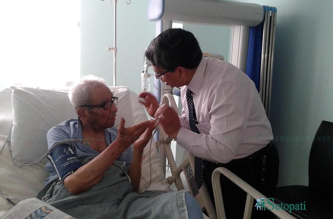 अस्पतालमा उपचाररत राष्ट्रकवि माधवप्रसाद घिमिरेको स्वस्थ्यबारे जानकारी लिँदै ग्रान्डी अस्पतालका डा. चक्रराज पाण्डे। तस्बिरः सेतोपाटी