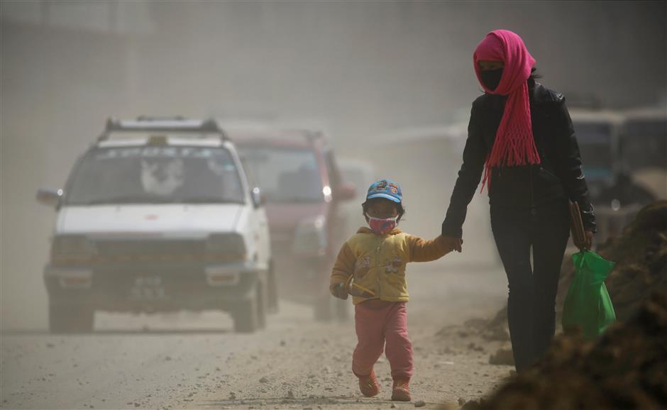 काठमाडौंको धूलोमा मास्क लगाएर हिँड्दै। तस्बिरः रोयटर्स