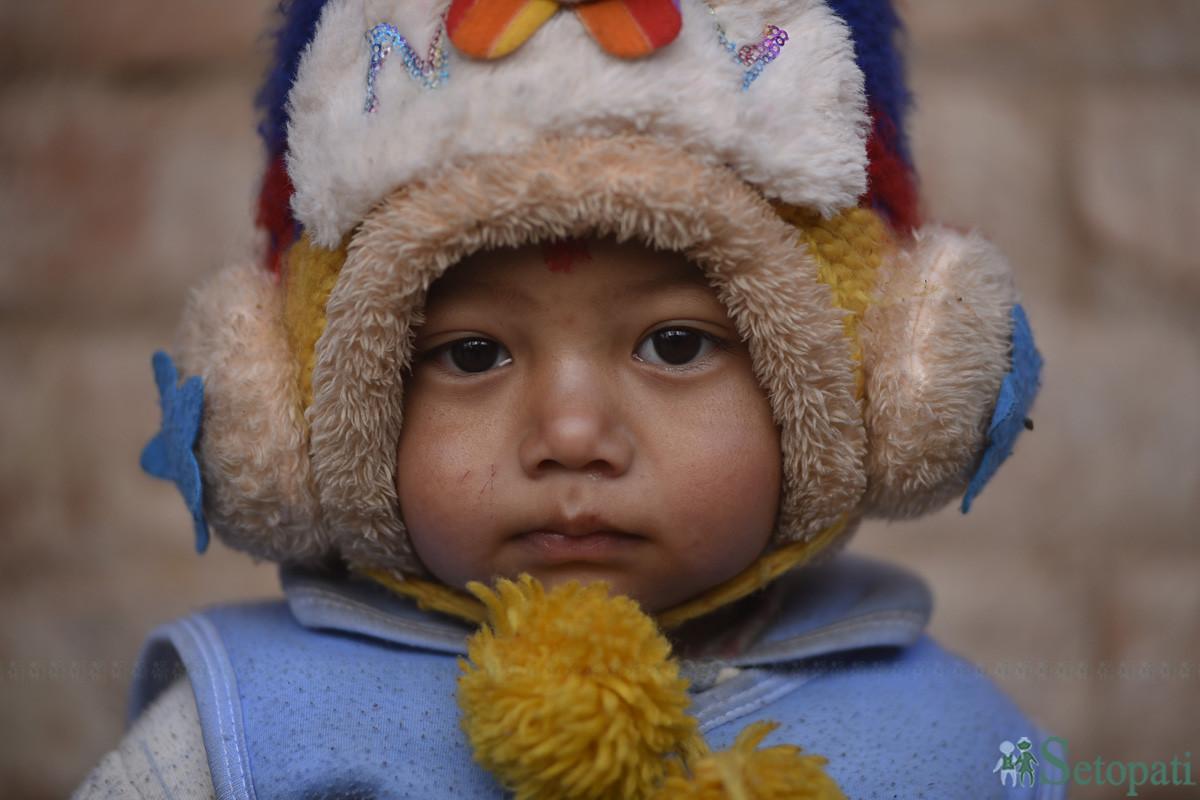 जाडो छल्नलाई न्यानो लुगा लगाएर बसेका एक बालक। तस्बिरः नारायण महर्जन