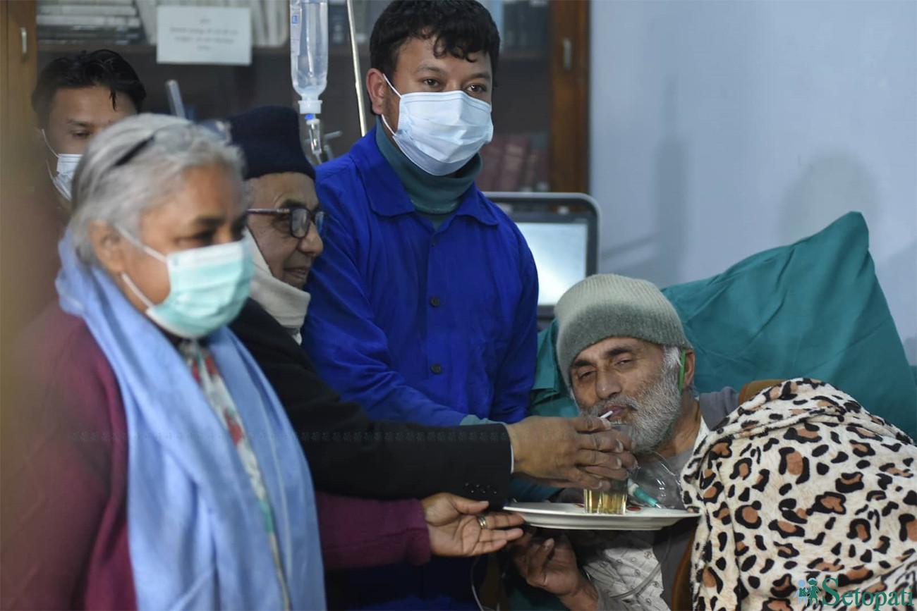 शिक्षण अस्पतालका सफाइ कर्मचारी, पूर्व प्रधानन्यायधीशको हातबाट  जुस पिएर अनसन तोड्दै डा. केसी।  तस्बिरः नारायण महर्जन
