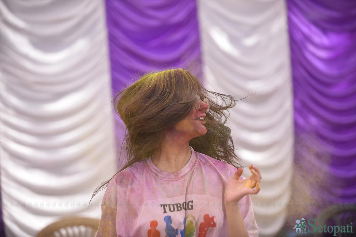 कुलेश्वर मारवाडी समाज र कुलेश्वर हनुमान सेवा समितिले आयोजना गरेको होली उत्सवमा रमाउदै एक युवती। तस्बिरः नारायण महर्जन