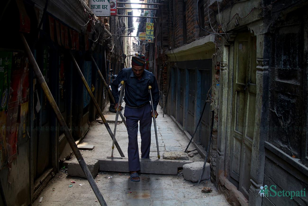 बसन्तपुरको एक गल्लीमा टेको लगाइएको घरहरूको बीचबाट बैसाखीको सहाराले हिँड्दै एक वृद्ध। तस्बिर: निशा भण्डारी/ सेतोपाटी