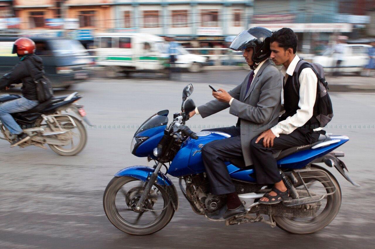 मोटरसाइकलमा मोबाइल फोन चलाउँदै। तस्बिरः सीताराम हाथेछू