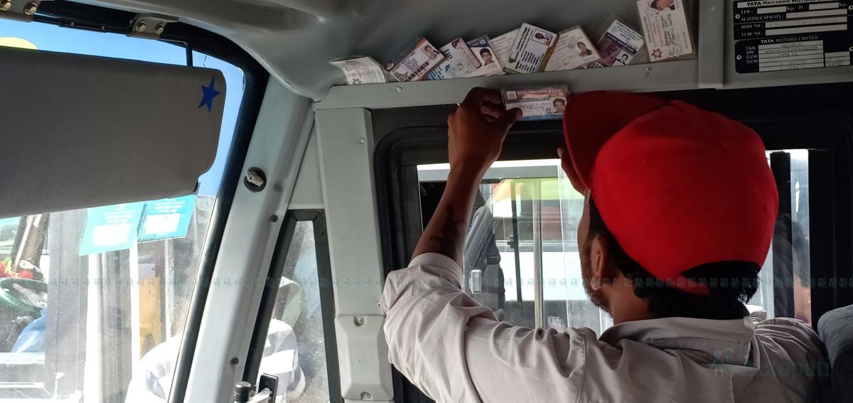 सहचालकले जफत गरेका नक्कली विद्यार्थी कार्ड मिलाउँदै एक सार्वजनिक बसका चालक। तस्बिर :   प्रशन्न पोखरेल/ सेतोपाटी