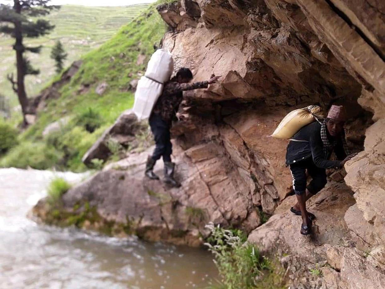 बाढीले काठेपुल बगाएसँगै जुम्लाको तिला गाउँपालिका– ६ र ७ मा जोड्ने पक्की पुल नहुँदा यहाँका स्थानीय बासिन्दा जोखिम मोल्दै कठिन बाटोमा सामान ओसारपसार गर्दै । तस्वीर: विजय रावत