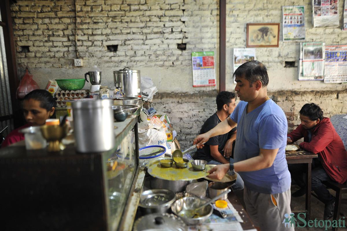 टेकराज पराजुली आफ्नो खाजा घरमा काम गर्दै। तस्बिरः नारायण महर्जन/सेतोपाटी