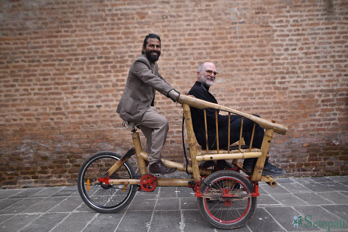 बाँसको साइकल प्रदर्शन गर्दै आबारीका नृपाल र अमेरिकी प्राध्यापक लान्स गोर्डन रेक। तस्बिर: नारायण महर्जन/सेतोपाटी