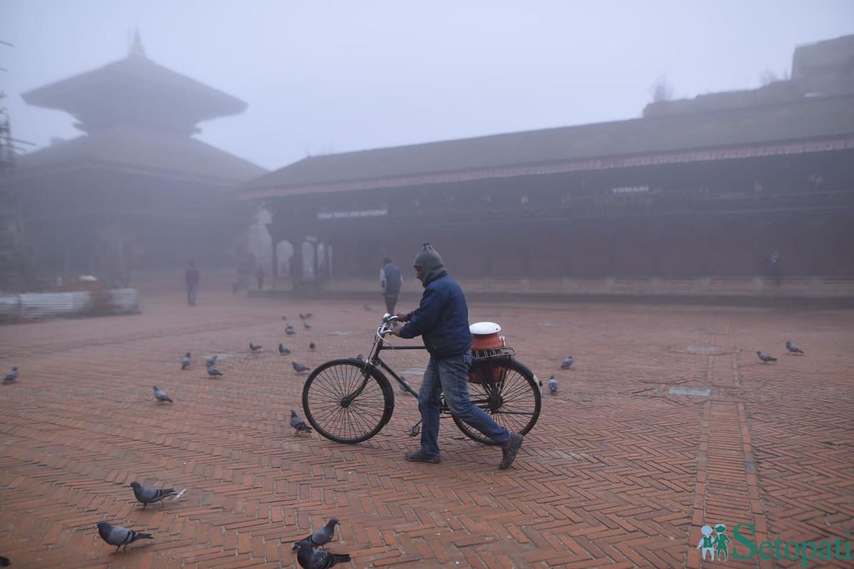 चिसो हुस्सुका बाबजुत भक्तपुर दरवारस्क्वायर परिसर हुँदै साइकल डोर्याएर गन्तव्यतिर लागेका एक यात्री। तस्बिरः नारायण महर्जन