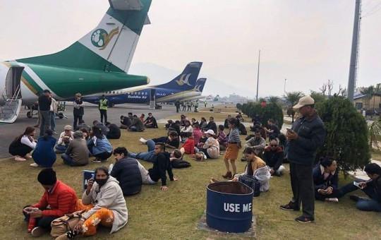 उडान डिले भएपछि पोखरा विमानस्थलमा जहाजकै छेउ बसिरहेका यात्रु। तस्बिर : आदर्श कर्णको फेसबुकबाट